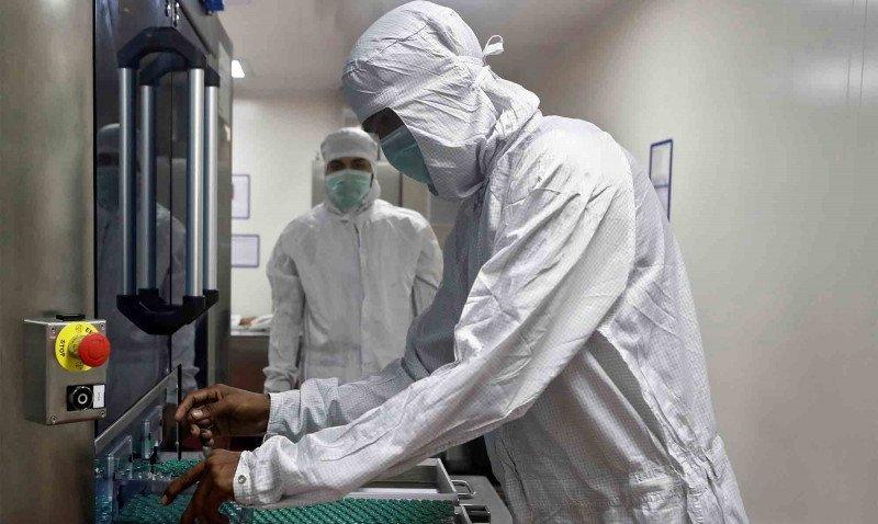 Petugas memindahkan botol-botol berisi vaksin COVID-19 AstraZeneca COVISHIELD melalui mesin pemeriksaan di sebuah laboratorium di Institut Serum India di Pune, India. Foto : Reuters